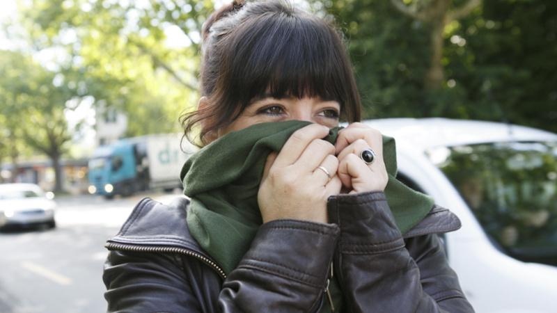 Heuschnupfen, Allergie, Pollenallergie: junge Frau in einer Stadt an einer vielbefahrenen Strasse, sie hat sich den grünen Schal über Mund und Nase gezogen