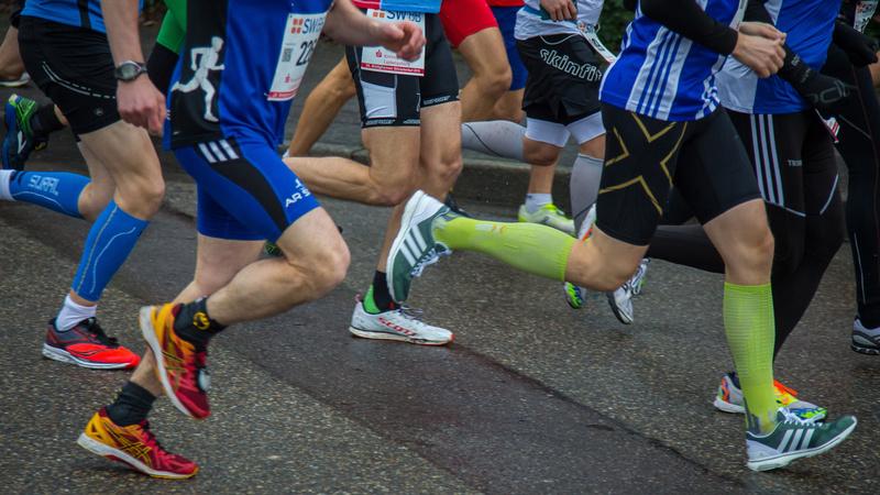 Des jambes de coureurs qui portent des bas de contention