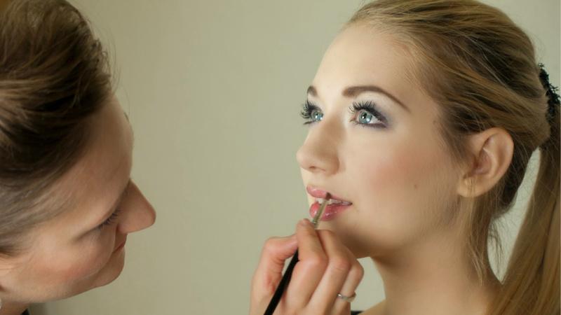 Schönheit, Pflege, Schminken, Kosmetik: Junge Frau mit langen blonden, zum Pferdeschwanz gebundenen Haaren wird von einer anderen Frau geschminkt.