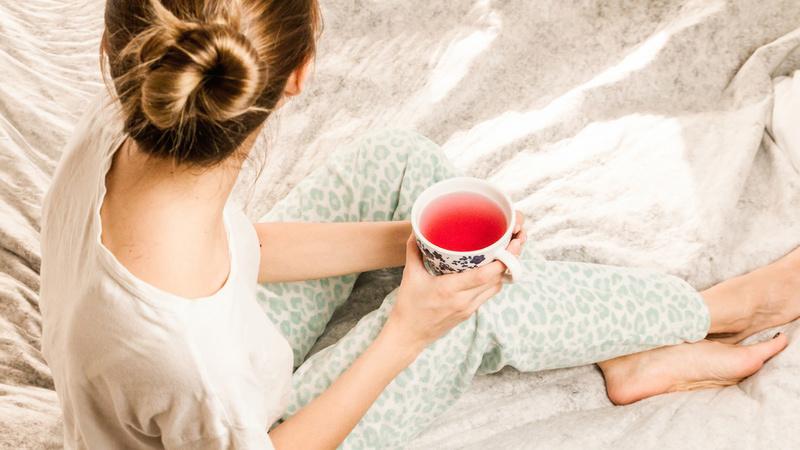 Bronchitis, Husten, Schleim: Eine blonde Frau hält eine Tasse Tee in beiden Händen und sitzt auf dem Bett.