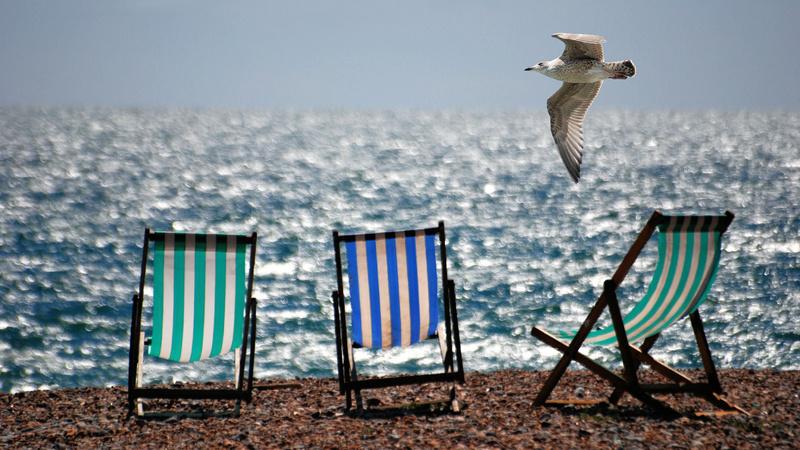 Meer, Heilkraft, Algen, Muscheln: Sandstrand, im Hintergrund das Meer, darauf drei Liegestühle mit gestreiften Stoffbezügen. Eine Möwe fliegt darüber.
