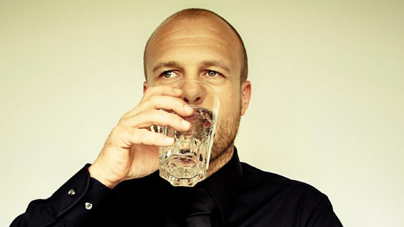 Ein Mann trinkt aus einem Glas Wasser.