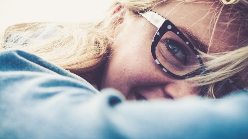 Akne, Pickel, unreine Haut: Jugendliche mit langen blonden Haaren und Brille, man sieht nur die Hälfte der rechten Gesichtshälfte. Sie hat den Kopf auf den Arm gebettet