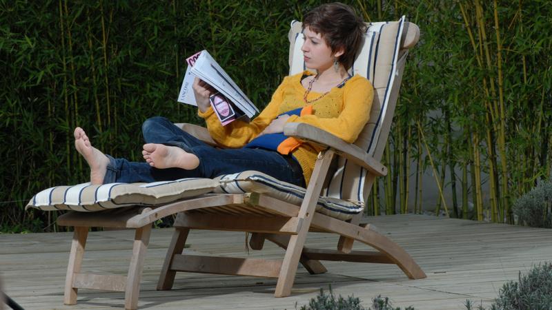 Menstruation, PMS, prämenstruelles Syndrom: Frau liegt auf einem Liegestuhl, sie liest eine Zeitschrift