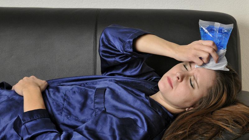 Kopfschmerzen, Migräne: Frau liegt auf dem Sofa, sie hält sich einen Eisbeutel an die Stirn und hat die Augen geschlossen