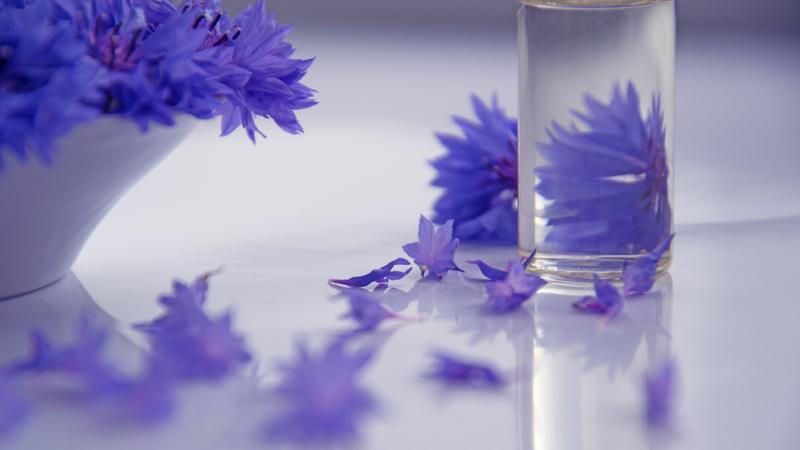 Ein durchsichtiges Fläschchen, darin eine klare Flüssigkeit. Im Hintergund durscheinend eine violette Blüte. Daneben steht eine Schale mit denselben violetten Blüten.
