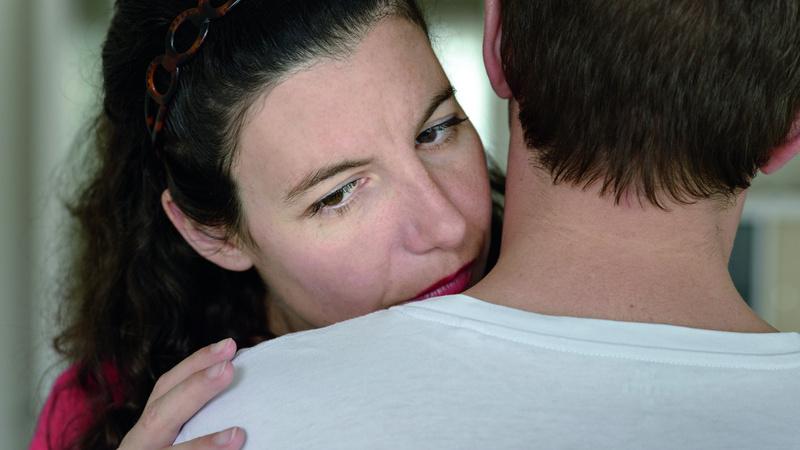 Duft, Geruch, Hormone: Schultern eines Mannes von hinten, ihm vis à vis eine Frau. Sie umarmt ihn und riecht an seinem Hals