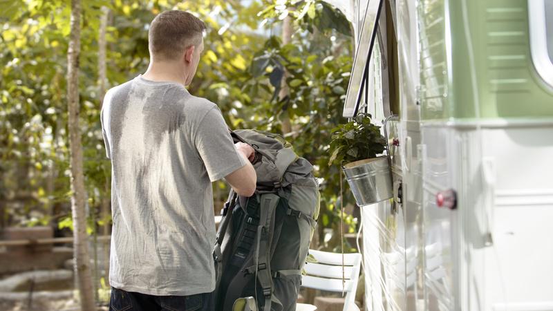 Schwitzen, Schweiss, Stinken: Mann in grauem T-Shirt von hinten, sein Rücken ist total verschwitzt. Er hat gerade seinen Rucksack abgelegt.