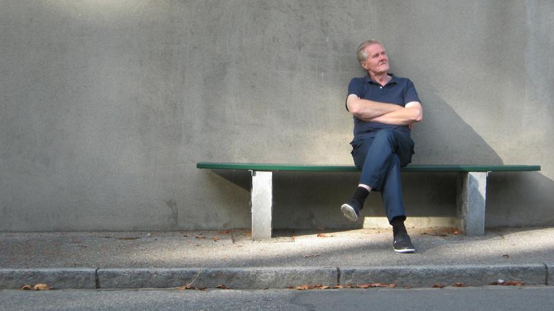 Prostata, Prostatabeschwerden: älterer Mann sitzt auf einer Bank, die Beine übereinandergeschlagen