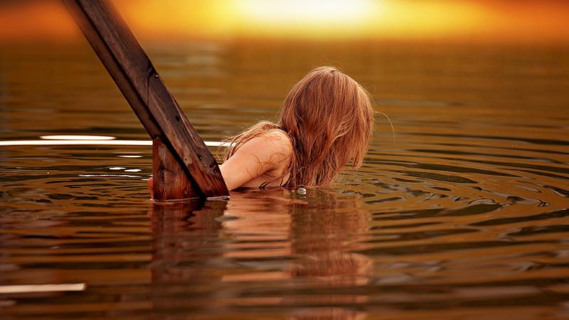 Wellness, Baden, Badetherapie: Frau steigt über eine Holztreppe in einen See, der im Abendrot daliegt