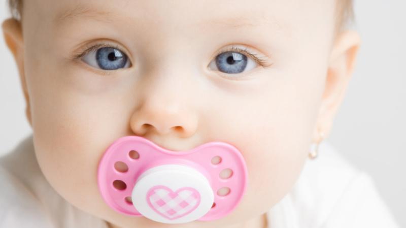Babyjahre, Baby, Säugling, Nuggi: Baby mit einem rosa-weissen Nuggi blickt in die Kamera