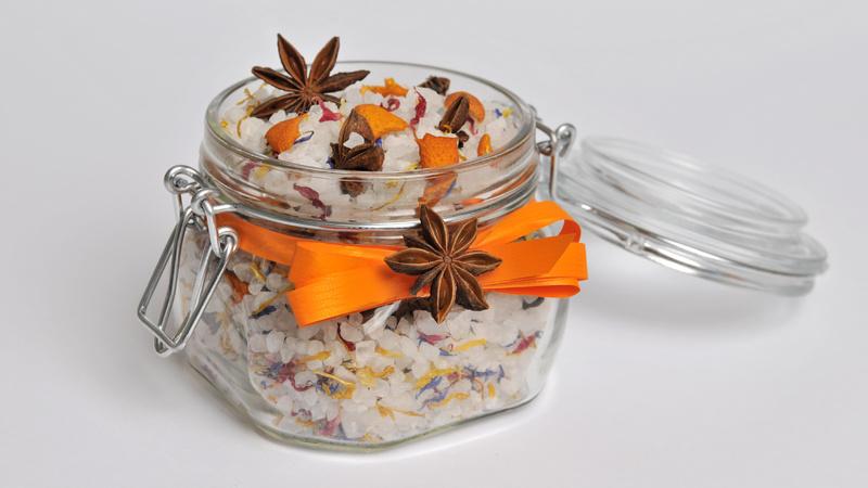 Wellness, Baden, Badezusatz: Deckelglas, gefüllt mit Badesalz, umwickelt mit einer orangefarbenen Schleife