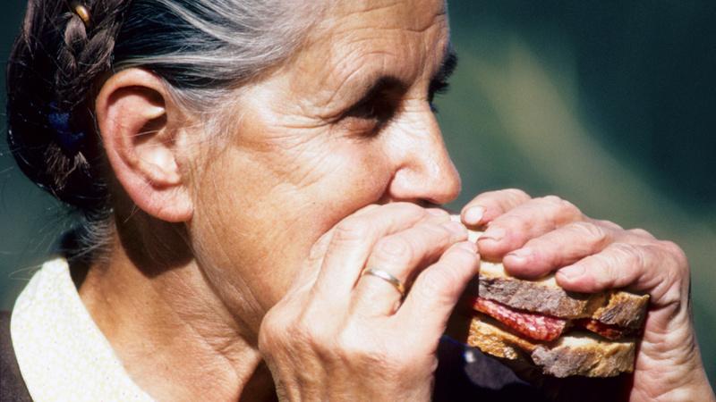 Senioren, Ernährung, Gesund: Seniorin beisst in ein Eingeklemmtes mit Salami