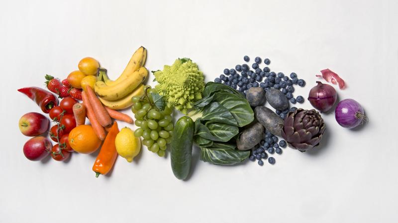Ernährung, Säure-Basen: Gemüse und Früchte, farblich assortiert von rot (links) über gelb und grün bis blau und violet (rechts