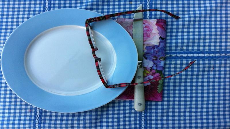 Ernährung, Fasten: Ein Porzellanteller, weiss mit blauem Rand, steht auf einer blau-weiss karierten Tischdecke, auf einer Papierserviette mit Blumenmotiv liegt ein Messer, auf dem Teller liegt eine Brille