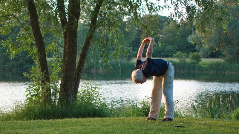 Rheuma, Gicht, Gelenkbeschwerden: Alter Mann macht im Park Dehungsübungen