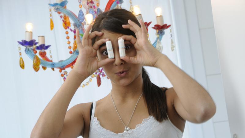 Menstruation, Periode, Teenager: Mädchen mit langen braunen Haaren und weissem Trägershirt hält sich zwei Tampons vor die Augen