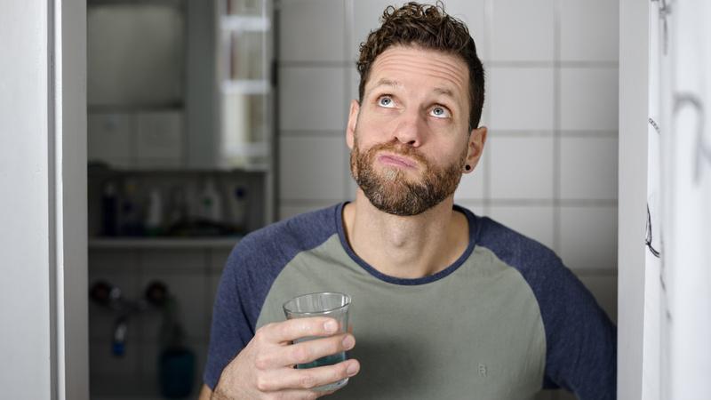 Mund, Mundpflege, Mundspülung: Junger Mann, hält Glas in der Hand und gurgelt