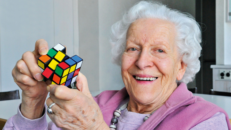 Une vieille dame s'amuse avec un Rubik's cube en souriant.