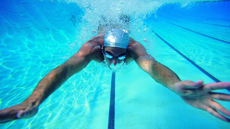 Fitness, Sport, Asthma: Unterwasseraufnahme eines Schwimmers mit Badekappe und Schwimmbrille. Er hat beide Arme weit von sich gestreckt