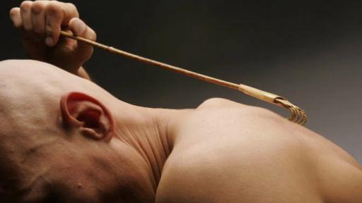 Un homme nu se gratte le dos avec une brosse.