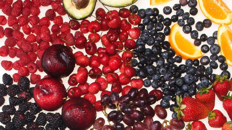 Ernährung, Mineralstoffe, Vitalstoffe: Viele verschiedene Beerensorten, dazu Orangen und Avocado liegen ausgebreitet auf einem weissen Hintergrund