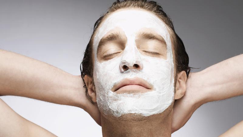 Schönheit, Pflege, Haut, Winter: junger Mann, die braunen kurzen Haare zurückgekämmt, die Hände im Nacken, Augen geschlossen trägt eine weisse Gesichtsmaske