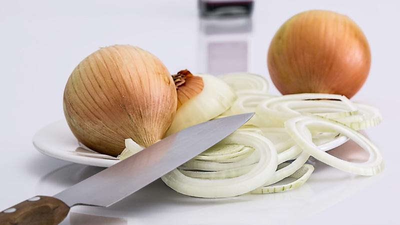 Verdauung, Blähungen, Flatulenz: Gelbe Zwiebeln, eine in Ringe geschnitten, zwei noch ganz und mit Schale. Ein grosses Küchenmesser liegt daneben