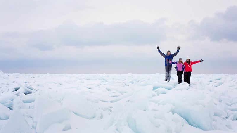 Körper, Durchblutung, Frieren: Eine Frau und zwei Kinder stehen in einer eisigen Schneelandschaft, sie sind dick angezogen und winken dem Fotografen zu. Der Himmel ist bedeckt