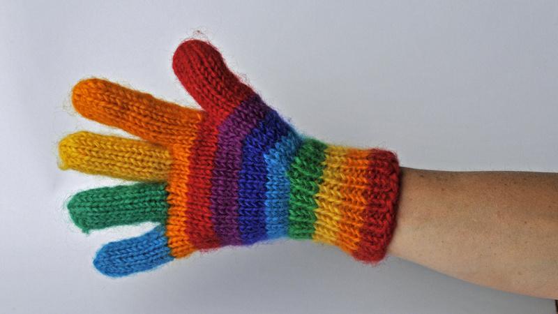 Körper, Durchblutung: Ein Arm, die Hand steckt in einem regenbogenfarbigen Handschuh