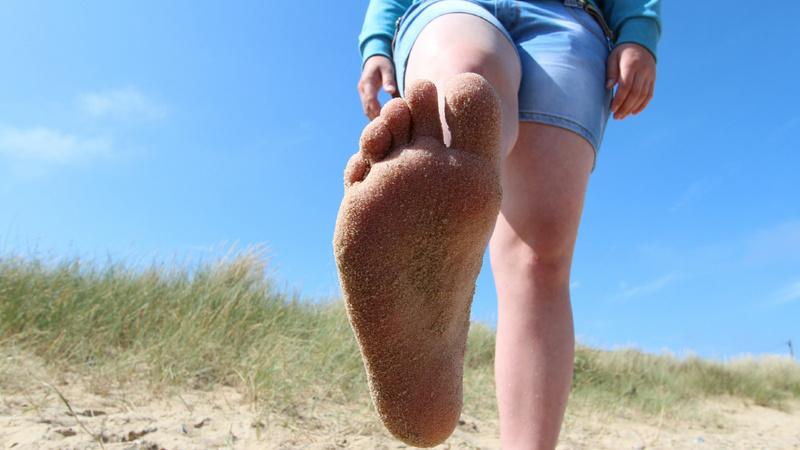 Körper, Füsse, Gelenke, Knochen: Junge Frau am Strand, wir sehen nur ihre Beine in kurzen Jeans. Sie hält den rechten Fuss in die Höhe, so dass die Fusssohle zu sehen ist.