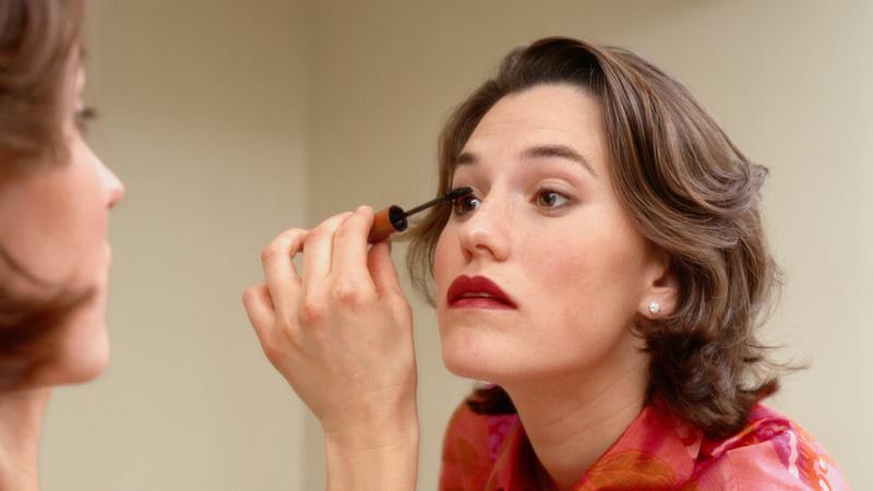 Schönheit, Pflege, Schminken, Make-up, wasserfest: Frau steht vor dem Spiegel und schminkt sich