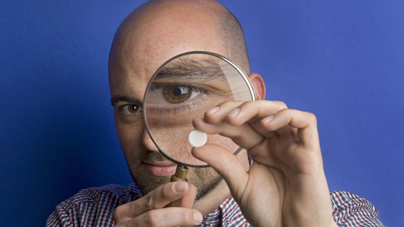 Naturheilkunde, Schüssler Salze: Mann mit Glatze betrachtet eine Tablette durch eine grosse Lupe