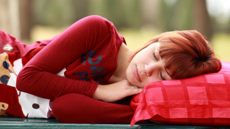 Ernährung, Säure-Basen, Übersäuerung: Frau mit kurzen roten Haare liegt auf einer Bank.