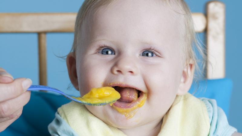 Ernährung, Babynahrung, Brei: Baby sitzt im Babystuhl und wird mit einem Löffel Brei gefüttert
