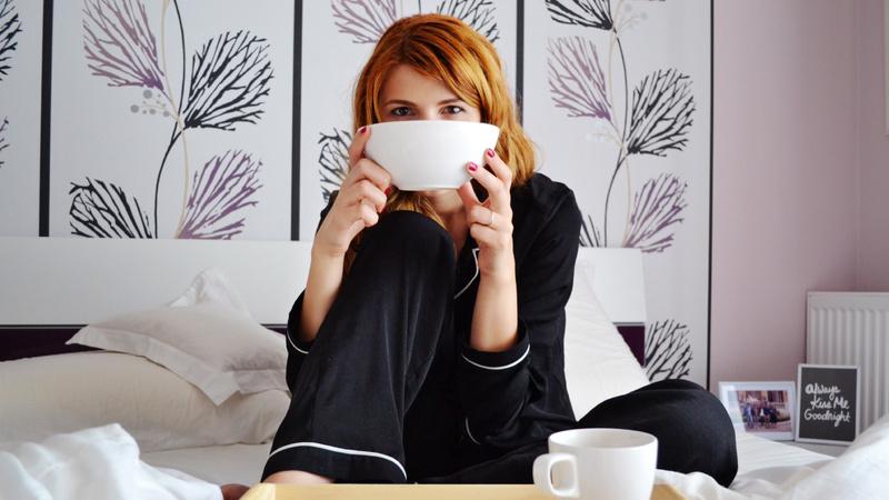 Wellness, Wohlfühlen: Frau sitzt im Pyjama im Bett und geniesst eine Tasse Tee