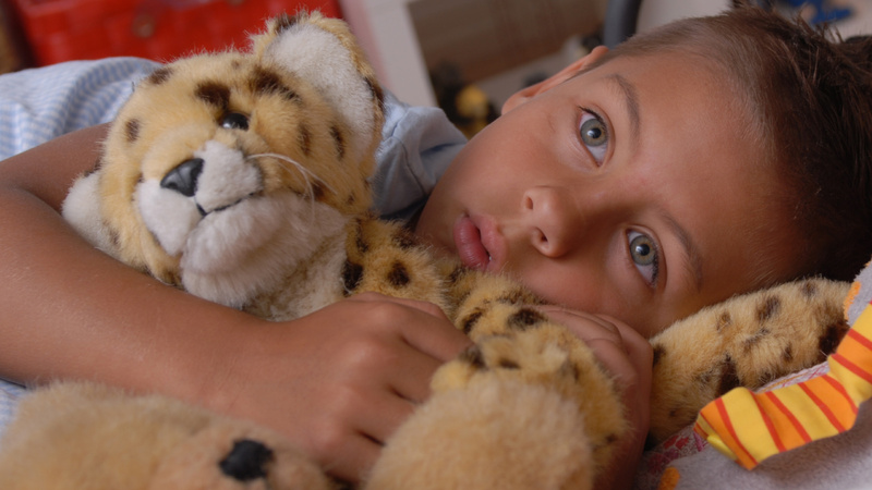 Ein kleiner Junge liegt im Bett mit seinem Plüsch-Leopart im Arm.