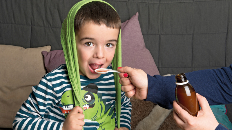Medikamente, Arzneimittel, Tabletten: Bub mit gestreiftem Pulli und einem grünen Tuch über dem Kopf bekommt von einer Frau mit rot lackierten Fingernägeln einen Sirup auf einem Plastiklöffel verabreicht.
