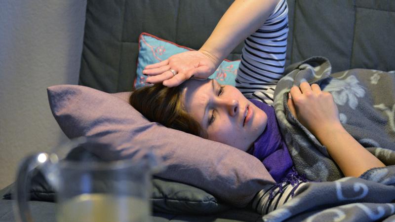 Fieber, erhöhte Temperatur: Junge Frau liegt auf dem Sofa, in eine Decke gehüllt. Sie trägt einen Schal und hält sich die linke Hand an die Stirn