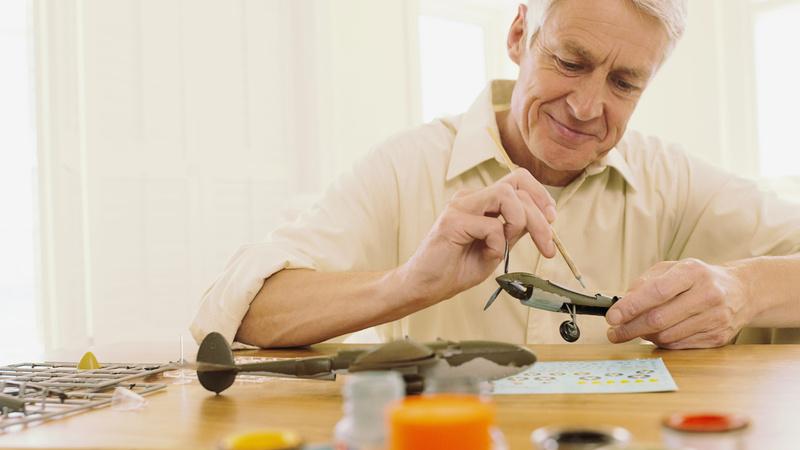 Psychologie, Stress, Entspannung, Alter: alter Mann sitzt an einem Tisch und baut ein Modellflugzeug