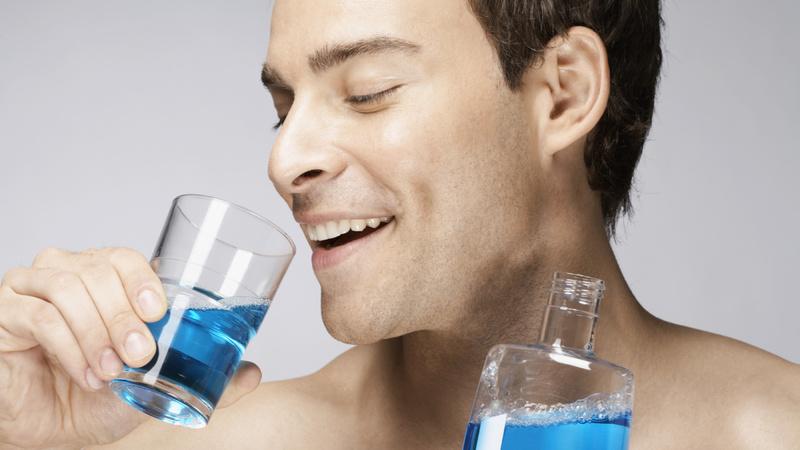 Schönheit, Pflege, Mundpflege, Mundspülung: Mann mit kurzen braunen Haaren hält ein Glas in der einen und eine Plasticflasche in der anderen Hand, in beiden ist eine bläuliche Flüssigkeit. Er setzt gerade zum Trinken an