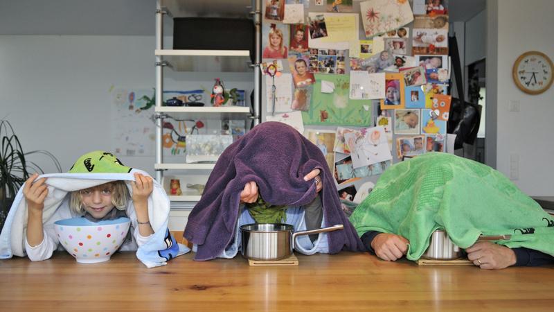 Erkältung, Schnupfen, Husten, Inhalieren: Zwei Erwachsene und ein Kind sitzen an einem Küchentisch und inhalieren.