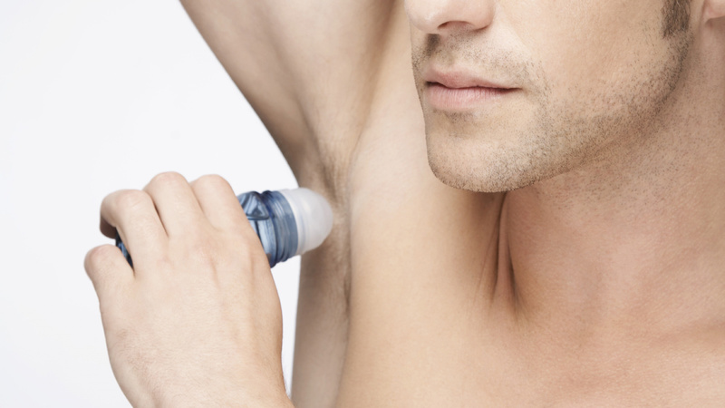 Schönheit, Pflege, Haut, Deo, Deodorant: Mann mit nacktem Oberkörper streicht sich Deo unter die rechte Achsel