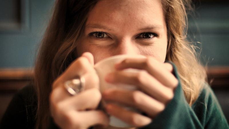 Ernährung, Tee, trinken: junge frau mit langen braunen Haaren hält eine weisse Porzellanteetasse in den Händen und trinkt daraus