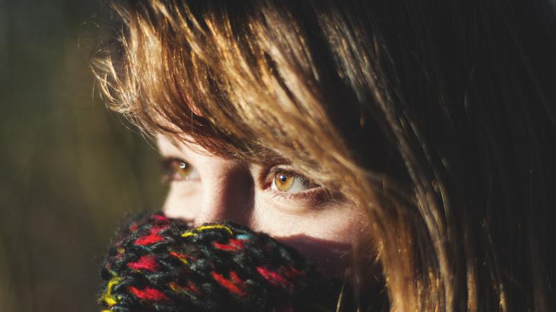 Erkältung, Heiserkeit, Stimme: Frau mit langen braunen Haaren hat sich einen grau-roten Schal vor den Mund gebunden, so dass nur ihre Augen zu sehen sind.