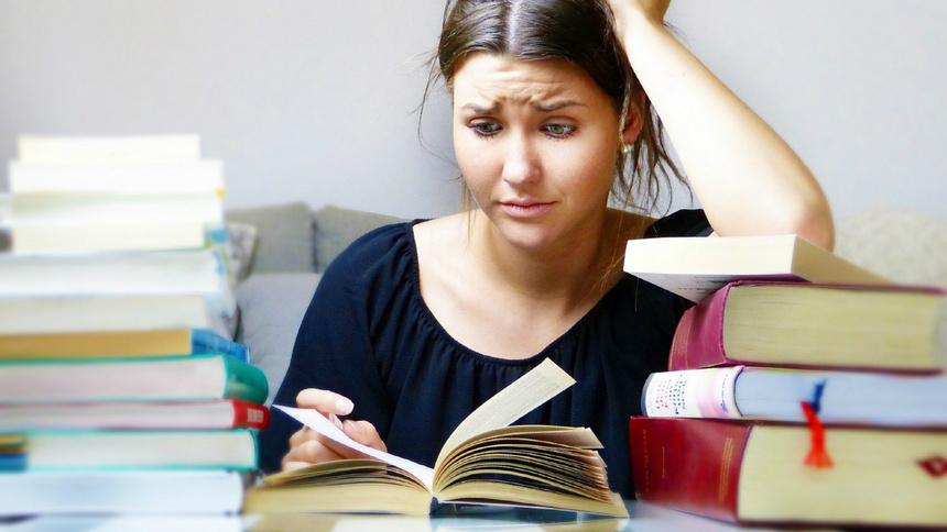 Stress, Angst, Prüfungen: eine Jugendliche sitzt an einem Pult, vor ihr stapelweise Bücher. Sie hat einen verzweifelten Gesichtsausdruck.