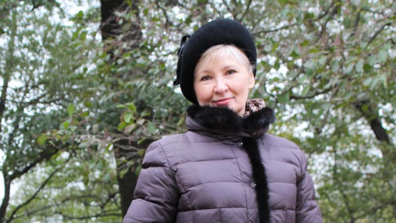 Schönheit, Pflege, Hautpflege, alt: Frau mittleren Alters, sehr gepflegt, steht in violetter Winterjacke mit schwarzer Mütze vor Bäumen