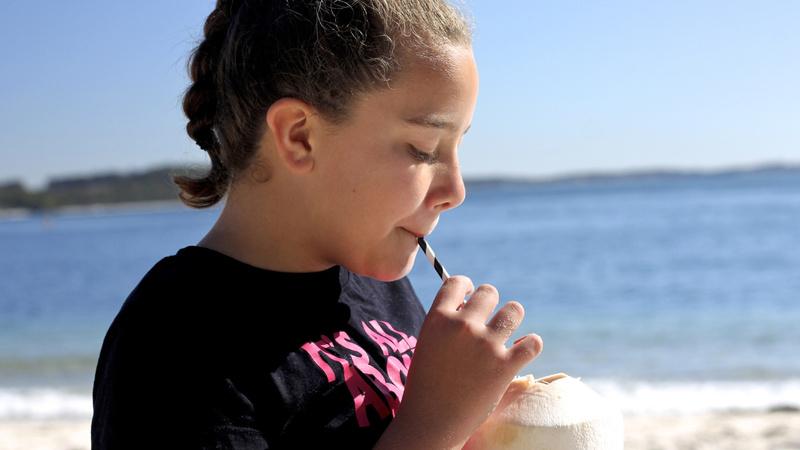Ernährung, Getränke, Kokoswasser: Mädchen an einem Meeresstrand, sie trägt ein schwarzes T-Shirt mit pinkfarbener Aufschrift. Sie hält eine aufgeschnittene Kokosnuss in der Hand, in der ein Röhrli steckt und sie trinkt daraus
