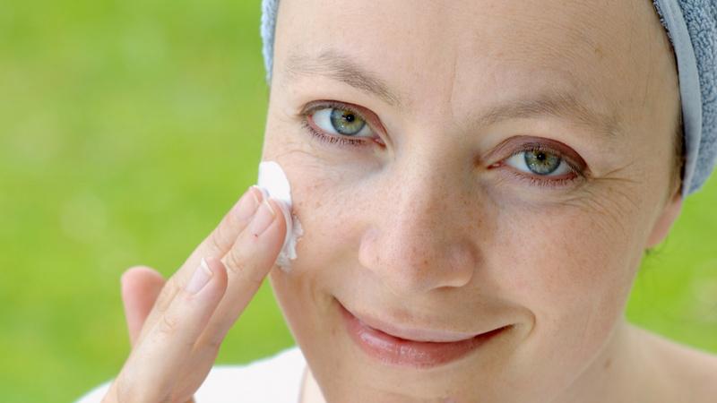 Eine Frau cremt ihr Gesicht ein.