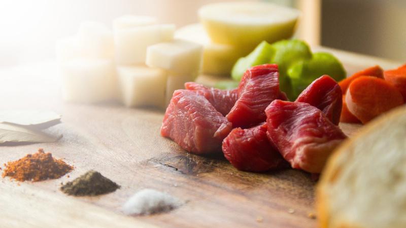 Ernährung, Mineralstoffe, Mikronährstoffe: geschnittenes Rindfleisch, davor Häufchen von Gewürzen auf einem Holzbrett